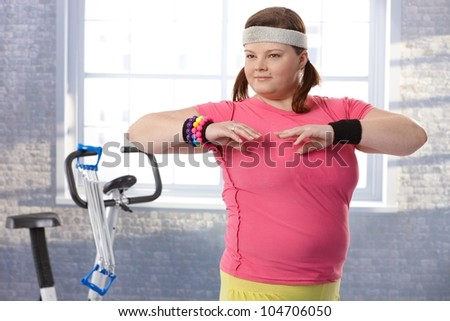 Overweight young woman exercising at the gym. - stock photo