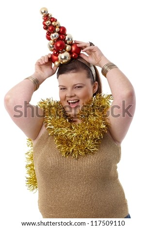 Overweight young woman holding a small christmas tree on head, smiling happily. - stock photo