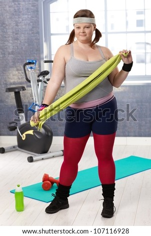 Overweight young woman prepared for workout at the gym. - stock photo