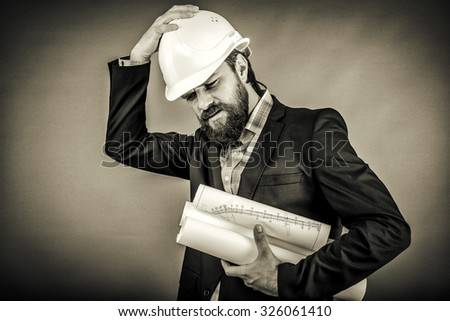 Overwhelmed architect with white hardhat over gray background - stock photo