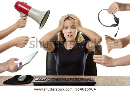 overwhelmed business woman sitting at her desk surrounded by many hands holding different objects - stock photo