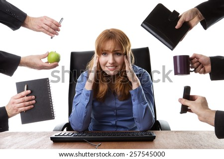 overwhelmed business woman sitting at her desk surrounded by many male hands holding different objects - stock photo