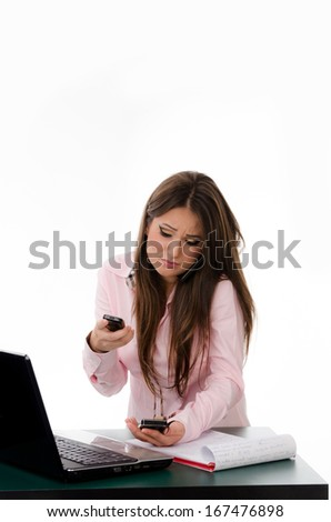 Overwhelmed business woman talking on multiple phones while working on the laptop  - stock photo