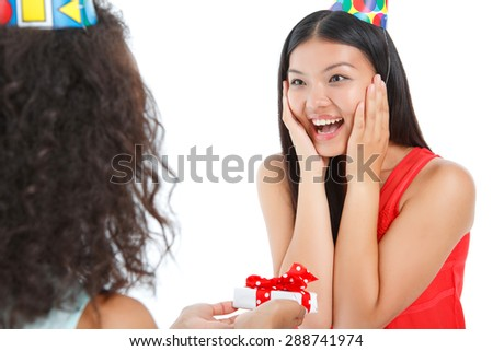 Overwhelming surprise. Exited positive girl holding her hand on her cheeks and looking at friend while receiving present - stock photo