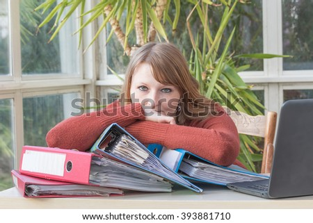Overworked  and frustrated caucasian young woman is sitting in a office. - stock photo