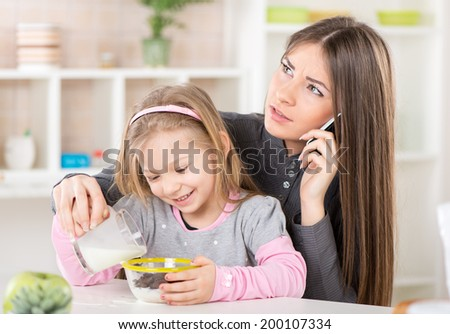 Overworked Business Woman and her little daughter in the morning. Overworked mother make phone calls before going to work. - stock photo