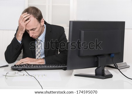 Overworked businessman frustrated and stressed in his office with computer - overtime. - stock photo