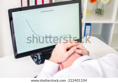 Overworked businessman holding his head in his hands - stock photo