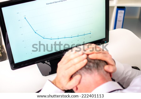 Overworked businessman holding his head in his hands