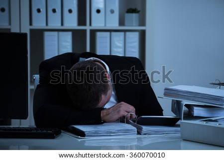 Overworked businessman leaning head on desk while working late in office - stock photo