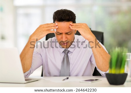 overworked businessman sitting in office - stock photo