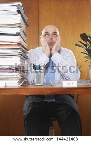 Overworked businessman sitting with hands on face by pile of documents at desk - stock photo