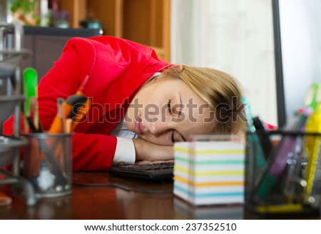 Overworked businessman sleeping in the office with her head on the table - stock photo