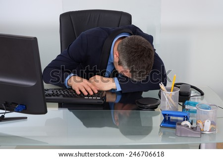 Overworked Businessman Sleeping On Desk At Office - stock photo