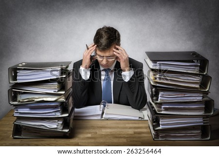 Overworked businessman with lot of files on his desk - stock photo