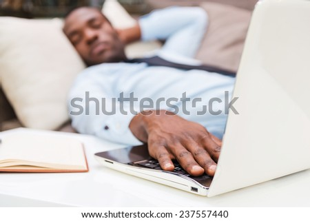 Overworked businessman. Young African man in formalwear holding hand on laptop keyboard while sleeping on the couch   - stock photo