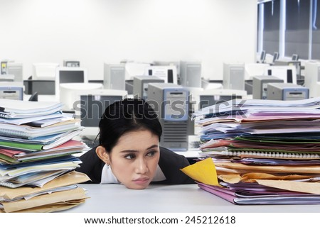 Overworked businesswoman with many jobs, looking at pile of documents with bored expression - stock photo