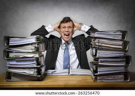 Overworked crying businessman with lot of files on his desk - stock photo