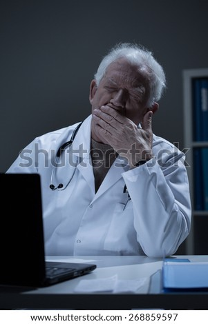 Overworked doctor sitting at the desk and yawning