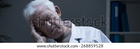 Overworked elder physician sleeping at work - panorama - stock photo