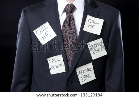 Overworked executive with sticky notes stuck on his suit reminding him of things to do - stock photo