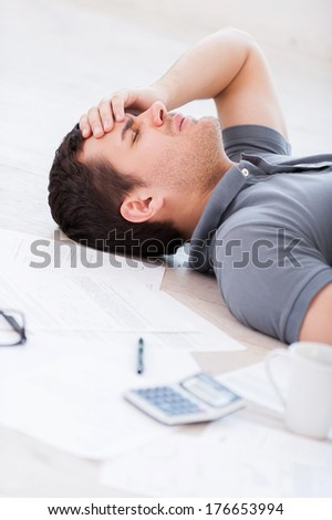Overworked man. Top view of depressed young man holding hand on forehead while lying on the floor with documents and coffee cup on it - stock photo
