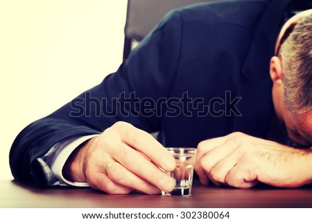 Overworked mature man drinking vodka in office. - stock photo