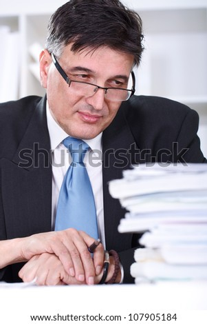Overworked senior businessman looking in stack of document - stock photo
