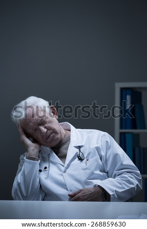 Overworked senior doctor sleeping in the office - stock photo