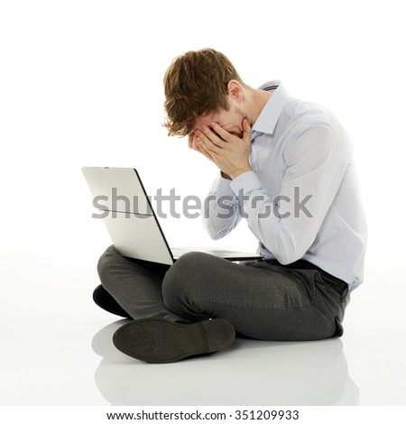 Overworked stressed and failing businessman with his laptop on white background