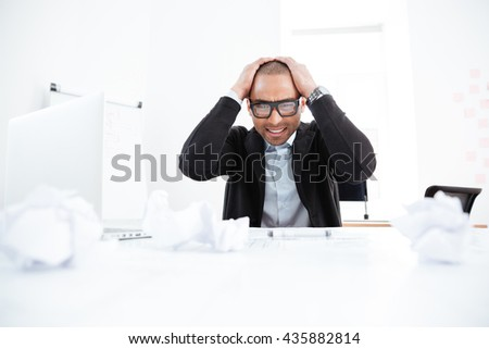 Overworked stressed businessman working on laptop computer and having headache - stock photo