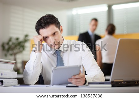 Overworked tired businessman sitting at his desk in the office using tablet computer - stock photo