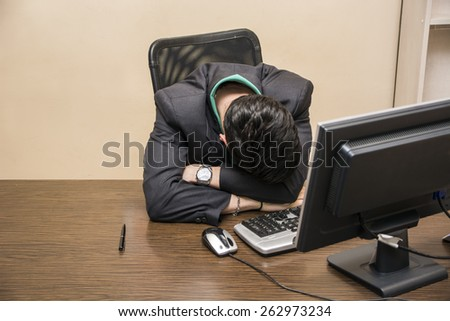 Overworked, tired young businessman sleeping on his desk  in office, in front of computer - stock photo