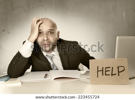 overworked unhappy bald Hispanic businessman in stress wearing suit and tie at office holding help sign working on desk with computer laptop looking frustrated and anxious - stock photo