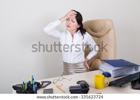 overworked woman with pain in office - stock photo