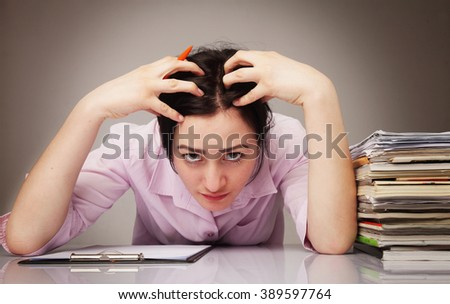 Overworked young businesswoman tearing hair out in frustrated anger (psychological portrait, frustration) - stock photo