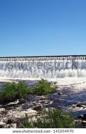 Owerflow of water on the man-made storage pond. Summer season - stock photo