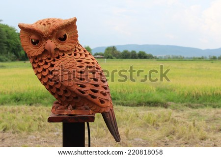 Owl in clay on wooden stick. - stock photo