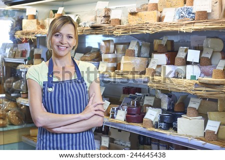 Owner Of Delicatessen Standing Next To Cheese Display - stock photo