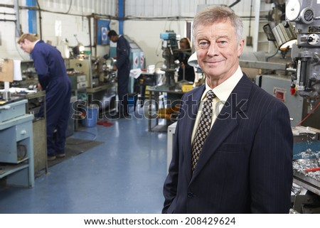 Owner Of Engineering Factory With Staff In Background - stock photo