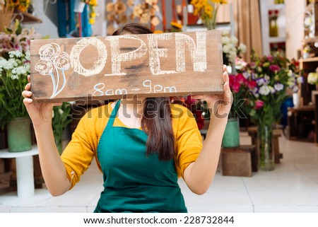 Owner of the shop posing with tablet sign - stock photo