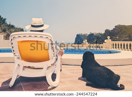 Owner relaxing by pool with dog beside him - stock photo