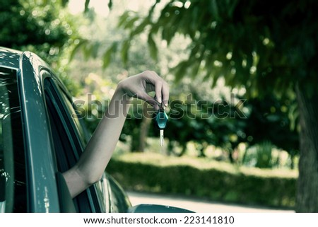 owner's hand with car key, vintage effect - stock photo