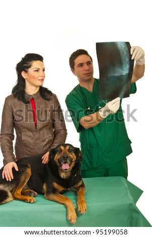 Owner woman with her dog having conversation with vet man and together looking on spine dog x-ray - stock photo