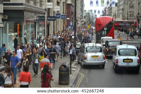 Oxford Street London circa 2014; Busy with crowds of shoppers walking next to shops, numerous black London taxis and few red double decker buses ,Oxford Street in Central London.