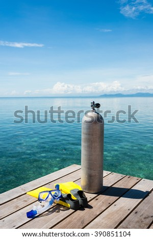 Oxygen cylinder with flippers and snorkel on pier. - stock photo