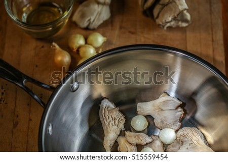 Oyster mushrooms and pearl onions being prepared for cooking