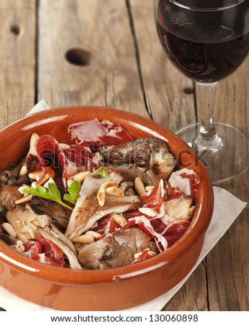 Oyster mushrooms, serrano ham and pine nuts tapas.  Setas con jamon y pinones with rioja red wine - stock photo