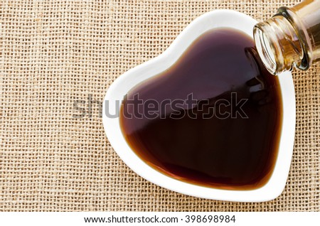 Oyster sauce in white bowl on sack background. - stock photo