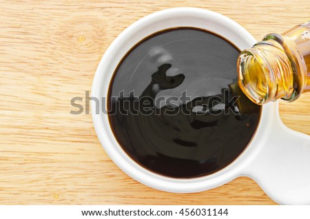 Oyster sauce in white bowl on wooden background. - stock photo